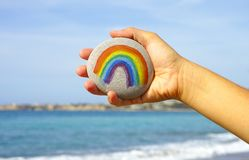 Mão da mulher que guarda o seixo com arco-íris pintado fotografia de stock