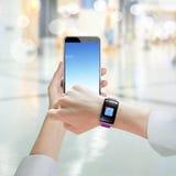 Mão da mulher que guarda o smartphone que veste o relógio esperto com ico do email Foto de Stock