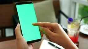 Mão da mulher que guarda o telefone esperto móvel com a tela verde vazia, corrediça do dedo do uso na tela verde na loja do café  imagem de stock royalty free