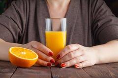 Mão da mulher que guarda o vidro do suco de laranja Fotos de Stock