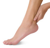 Mão da mulher que guarda seu pé saudável bonito e que faz massagens o tornozelo na área da dor foto de stock royalty free