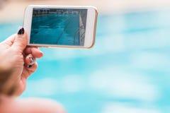 Mão da mulher que guarda suas atividades da piscina da gravação do telefone Imagens de Stock