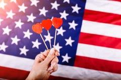 A mão da mulher que guarda três corações vermelhos dá forma na vara na frente da bandeira americana Conceito visual da preparação Imagens de Stock