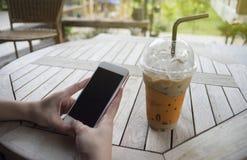 Mão da mulher que guarda um smartphone com a tela do preto do isolado, no café do café, foco seletivo, efeito da luz adicionado fotos de stock