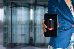Mão da mulher que guarda um telefone do toque com baixa bateria em uma tela Fotos de Stock Royalty Free