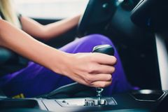 Mão da mulher que guarda uma engrenagem ao conduzir como um membro fotos de stock royalty free