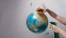 A mão da mulher que guarda uma esponja e um pulverizador para cancelar a terra do planeta O conceito de melhorar o estado do ambi imagem de stock
