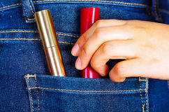 Mão da mulher que guarda uns batons vermelhos e dourados dentro do bolso traseiro das calças de brim Imagens de Stock
