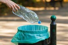 Mão da mulher que joga a garrafa plástica no escaninho de reciclagem, desordem de ambiental Imagens de Stock Royalty Free