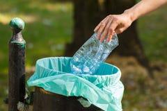 Mão da mulher que joga a garrafa plástica no escaninho de reciclagem, desordem de ambiental Fotos de Stock Royalty Free