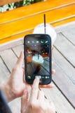 Mão da mulher que joga o smartphone e o café na tabela de madeira Foto de Stock