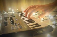 Mão da mulher que joga o teclado de midi do piano ou do electone, a chave branca e preta do sintetizador musical eletrônico Foto de Stock