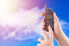 Mão da mulher que mantém botões velhos do telefone celular e das imprensas contra o fundo agradável do céu azul com luz solar imagem de stock