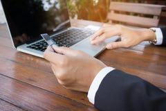 Mão da mulher que mantém o cartão de crédito pago em linha e o tom do vintage do portátil do uso Imagem de Stock Royalty Free