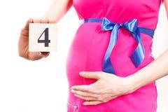 Mão da mulher que mostra o número de quarto mês da gravidez, esperando para o conceito recém-nascido Imagem de Stock