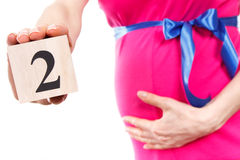 Mão da mulher que mostra o número de segundo mês da gravidez, esperando para o conceito recém-nascido Imagem de Stock Royalty Free
