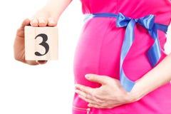 Mão da mulher que mostra o número de terceiro mês da gravidez, esperando para o conceito recém-nascido Imagem de Stock