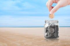 Mão da mulher que põe uma moeda sobre o fundo da natureza da praia, economia, conceito do dinheiro da economia imagem de stock