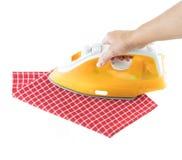 Mão da mulher que passa a toalha de cozinha quadriculado branca vermelha com o ferro amarelo no branco isolado foto de stock royalty free
