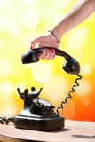 Mão da mulher que pendura acima do monofone Fotografia de Stock