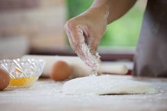 Mão da mulher que polvilha a farinha branca na massa Foto de Stock Royalty Free