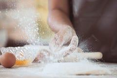 Mão da mulher que polvilha a farinha branca na massa Fotografia de Stock