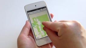 Mão da mulher que procura o mapa com o indicador no dispositivo esperto filme
