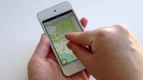Mão da mulher que procura o mapa com o indicador no dispositivo esperto