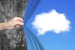 Mão da mulher que puxa a cortina azul da nuvem branca que cobre a parede velha Foto de Stock