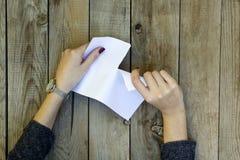 Mão da mulher que rasga o Livro Branco imagens de stock royalty free