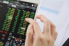 Mão da mulher que troca em linha na tabuleta com o papel de negócio e o coff Imagem de Stock Royalty Free