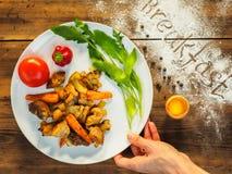 A mão da mulher s pôs sobre as batatas assadas da tabela com carne e alface sobre uma placa branca, vista superior Ainda vida dos Imagens de Stock