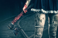 A mão da mulher suja que guarda um machado ensanguentado Imagens de Stock Royalty Free