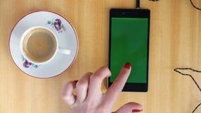Mão da mulher da tela do verde de Smartphone video estoque