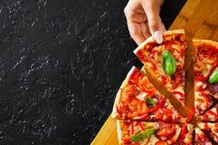 A mão da mulher toma uma parte de pizza com mozzarella, presunto, tomates, salame, pimenta, pepperoni, especiarias e manjericão f imagem de stock