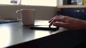 A mão da mulher usa o smartphone na mesa vídeos de arquivo