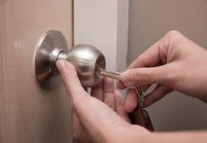 A mão da mulher usando a chave para destravar ou travar a porta branca foto de stock