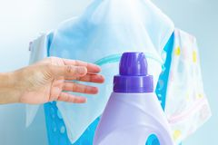 Mão da mulher usando o pano líquido da lavagem do detergente do emoliente da lavanderia imagem de stock royalty free