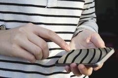 Mão da mulher usando o smartphone imagem de stock