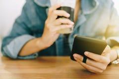 Mão da mulher usando o smartphone ao beber o café com máscara colorida do destaque da loja do café para objetar o backgroun bonit fotos de stock