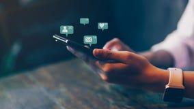 Mão da mulher usando o smartphone e meios sociais do ícone da tecnologia da mostra imagens de stock royalty free