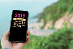 Mão da mulher usando o smartphone para fazer o planeamento à aplicação digital do calendário Conceito da tecnologia de comunicaçã imagem de stock royalty free