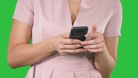 Mão da mulher usando um telefone esperto em uma tela verde, chave do croma vídeos de arquivo