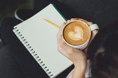 Mão da mulher da vista superior que guarda o copo de café quente do cappuccino com coração foto de stock