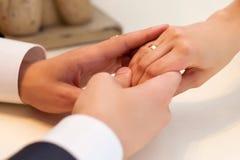 A mão da noiva com um anel em seu noivo da mão Fotos de Stock Royalty Free
