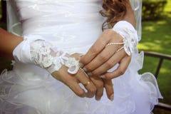 A mão da noiva com um bracelete do laço Fotografia de Stock
