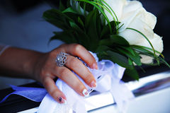 A mão da noiva com um ramalhete das flores Imagens de Stock
