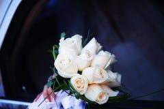 A mão da noiva com um ramalhete das flores Fotos de Stock Royalty Free