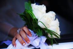 A mão da noiva com um ramalhete das flores Imagem de Stock Royalty Free