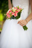 A mão da noiva com um ramalhete no fundo do vestido Imagens de Stock Royalty Free